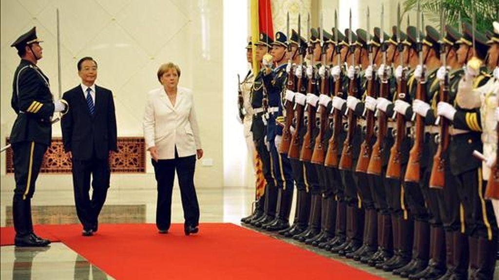 El primer ministro chino, Wen Jiabao (i) y la canciller alemana, Angela Merkel (d), pasan revista a la guardia de honor durante una reunión en el Gran Palacio del Pueblo en Pekín, China, hoy, viernes 16 de julio de 2010. Merkel realiza una visita oficial a China. EFE
