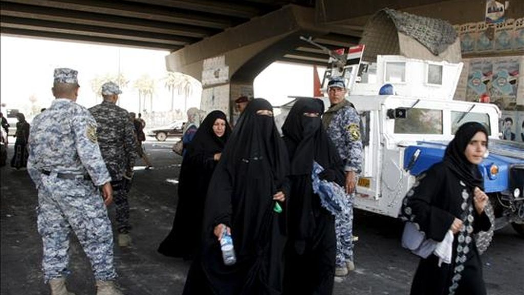 Policías iraquíes vigilando a un grupo de chiíes este martes en su peregrinación hacia la tumba del imán Musa al Kazem para marcar el aniversario de su muerte, en el distrito de Al Kazemiya, en Irak. EFE