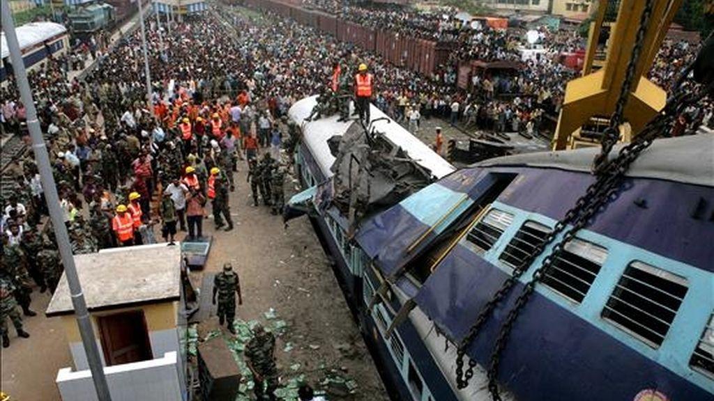 Soldados indios y miembros de los equipos de rescate trabajan en el lugar del choque de un tren de pasajeros que se dirigía a Calcuta contra otro que estaba detenido en una estación ferroviaria del Estado nororiental indio de Bengala, este lunes. EFE