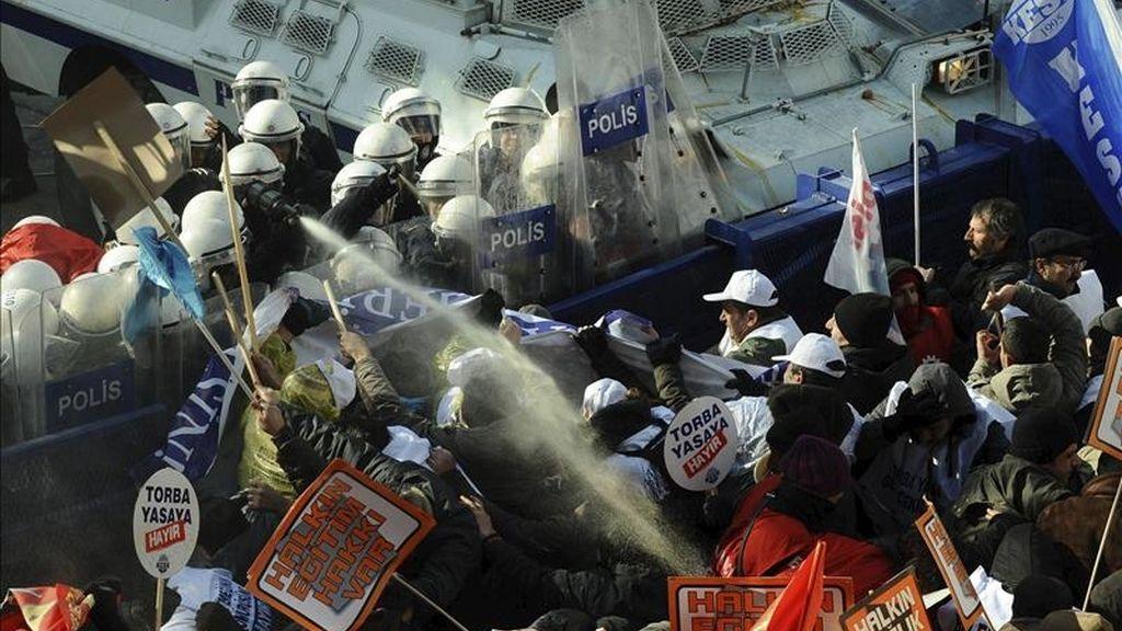 Trabajadores turcos y las fuerzas policiales antidisturbios se enfrentan durante una manifestación en contra del gobierno, en Ankara, Turquía. EFE