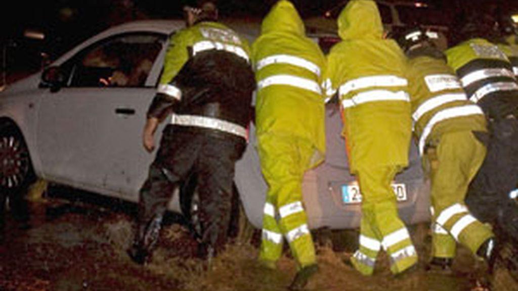 Varios operarios empujan un coche atrapado por las fuertes lluvias en Sevilla. Foto: EFE