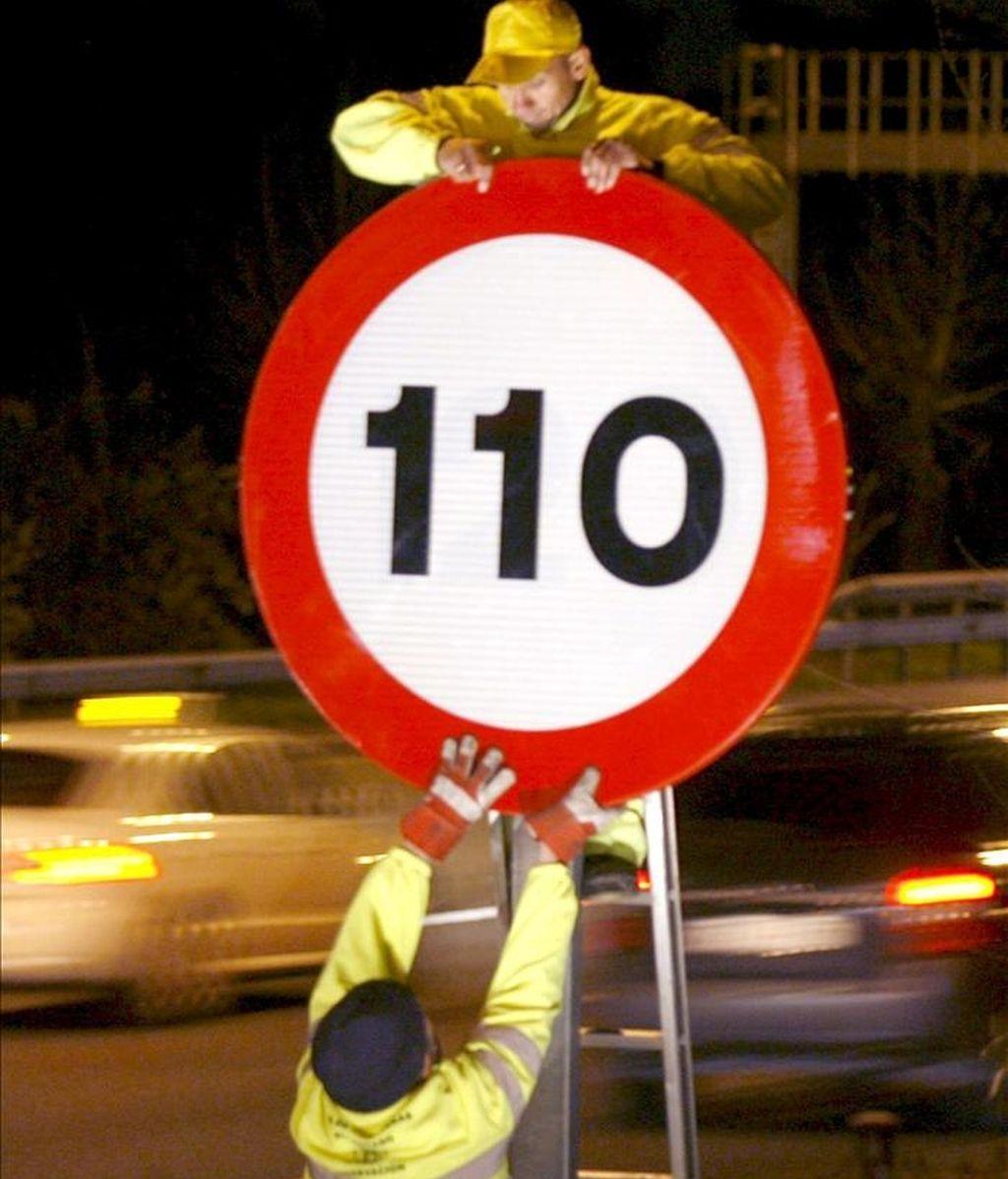 Varios operarios colocan el límite de velocidad de 110 kilómetros/hora en una señal de la A-2 situada en el kilómetro 6, en Madrid. EFE/Archivo