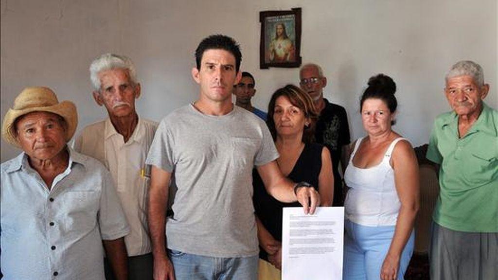 """El disidente cubano Silvio Benítez (c), activista de la """"Red Ciudadana Voces del Barrio"""", y otros opositores al Gobierno posan mostrando una copia de la carta enviada a la Asamblea Nacional. EFE"""