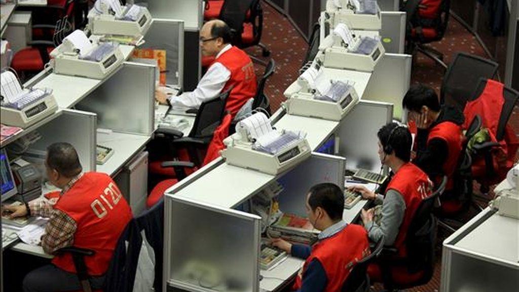 Trabajadores de la Bolsa de Hong Kong realizan sus labores en el parqué. EFE/Archivo