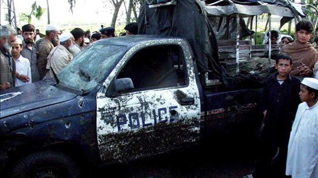 Varias personas observan los restos de un vehículo tras un atentado suicida en un puesto de control en el distrito de Charsada, situado en la Provincia de la Frontera del Noroeste (NWFP) en Pakistán, el pasado 16 de abril. EFE/Archivo