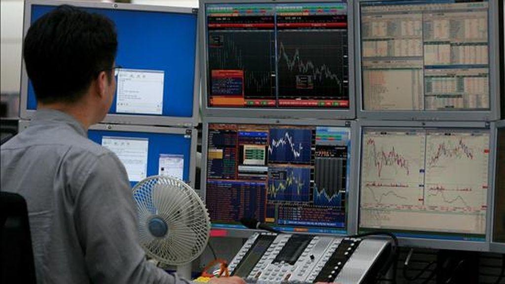 Un hombre observa un panel con las divisas y la cotización de la bolsa en Seúl. EFE