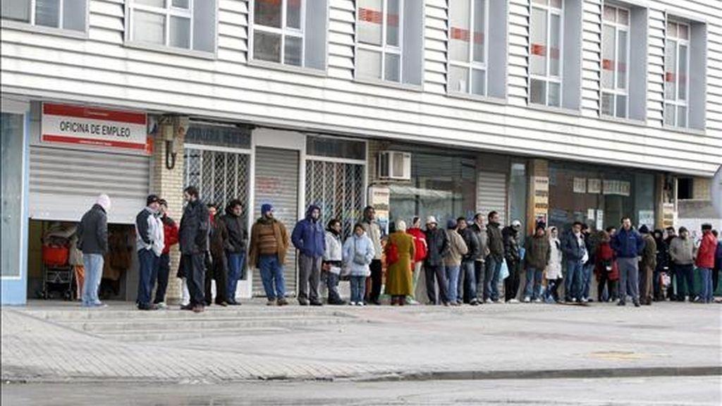 Varias personas forman una larga cola ante una oficina del INEM. EFE/Archivo