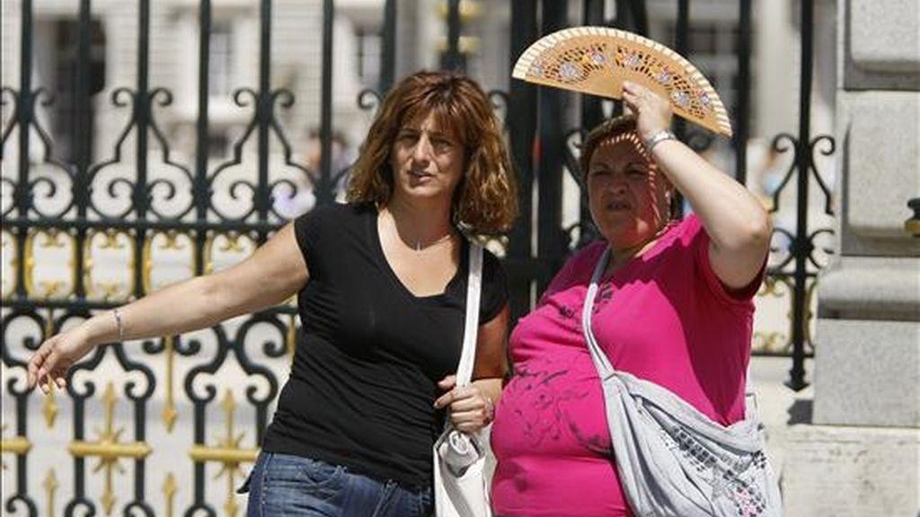 Unas señoras se protegen del sol con un abanico. EFE/Archivo