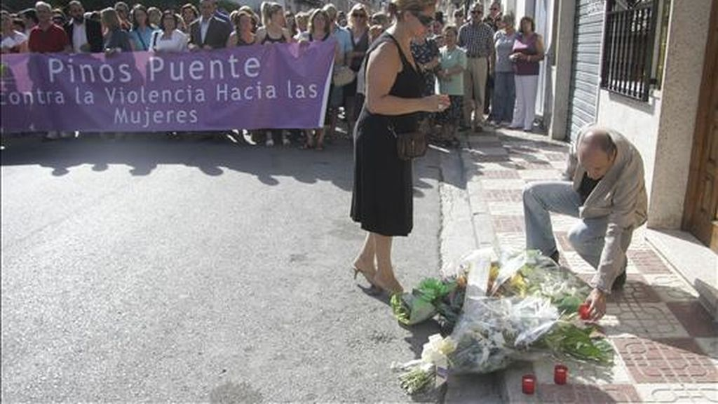 Algunos de los participantes este viernes en una manifestación en la localidad granadina de Pinos Puente depositando flores en el lugar donde este viernes una mujer de 42 años murio, presuntamente agredida por su ex pareja. EFE