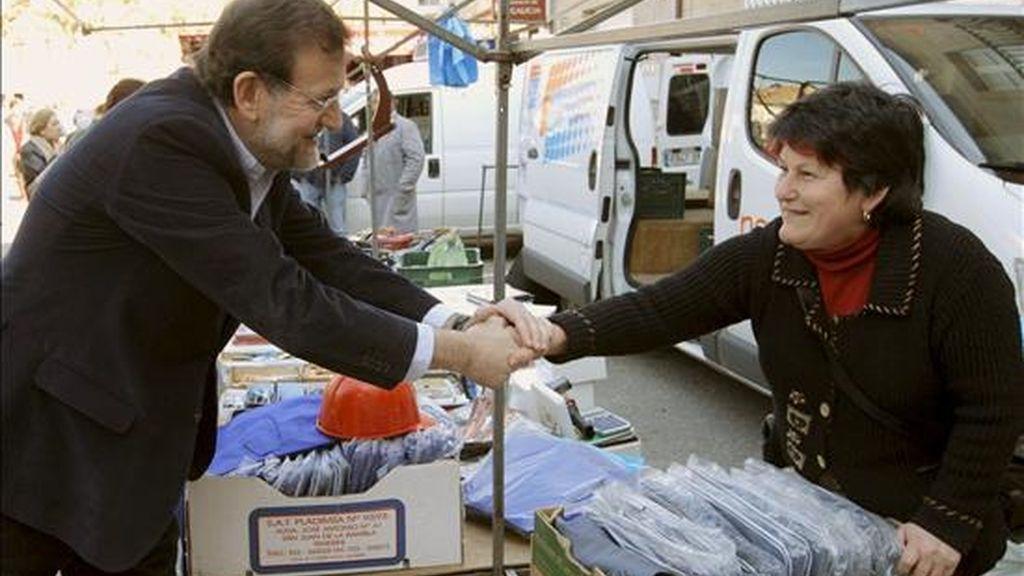 El presidente del Partido Popular, Mariano Rajoy, saluda a una venderora durante una visita a un mercadillo pontevedrés en febrero de 2009. EFE/Archivo