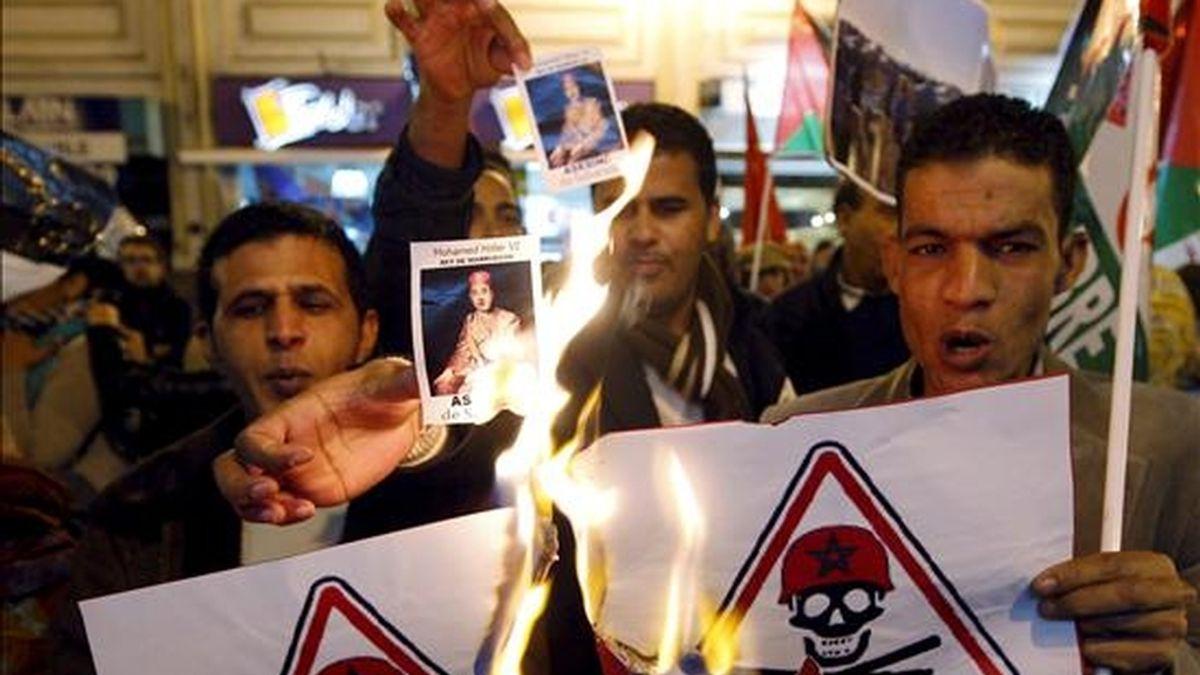 """Manifestantes quemando fotografías del rey Mohamed VI durante la concentración de activistas saharauis esta tarde ante el Consulado Marroquí en Valencia para protestar por """"el silencio del Gobierno español"""" tras los incidentes en El Aaiún. EFE"""