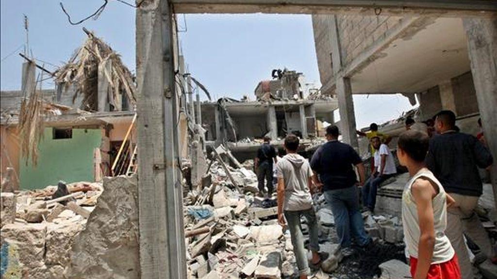 Varios palestinos observan los daños en sus viviendas tras una explosión registrada el lunes, en la casa de un líder de Hamás en el centro de la franja de Gaza. EFE/Archivo