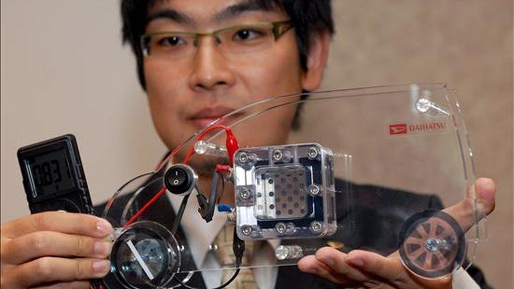 El ingeneriero del departamento de investigación de la compañía Daihatsu Motor Co., presenta una maqueta de coche que se impulsa utilizando una nueva tecnología de células de energía en Tokio (Japón). EFE/Archivo