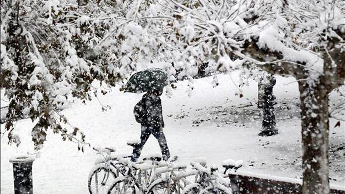 Un hombre camina esta mañana por la Plaza del Castillo de Pamplona durante la intensa nevada que ha caído sobre la capital navarra. EFE