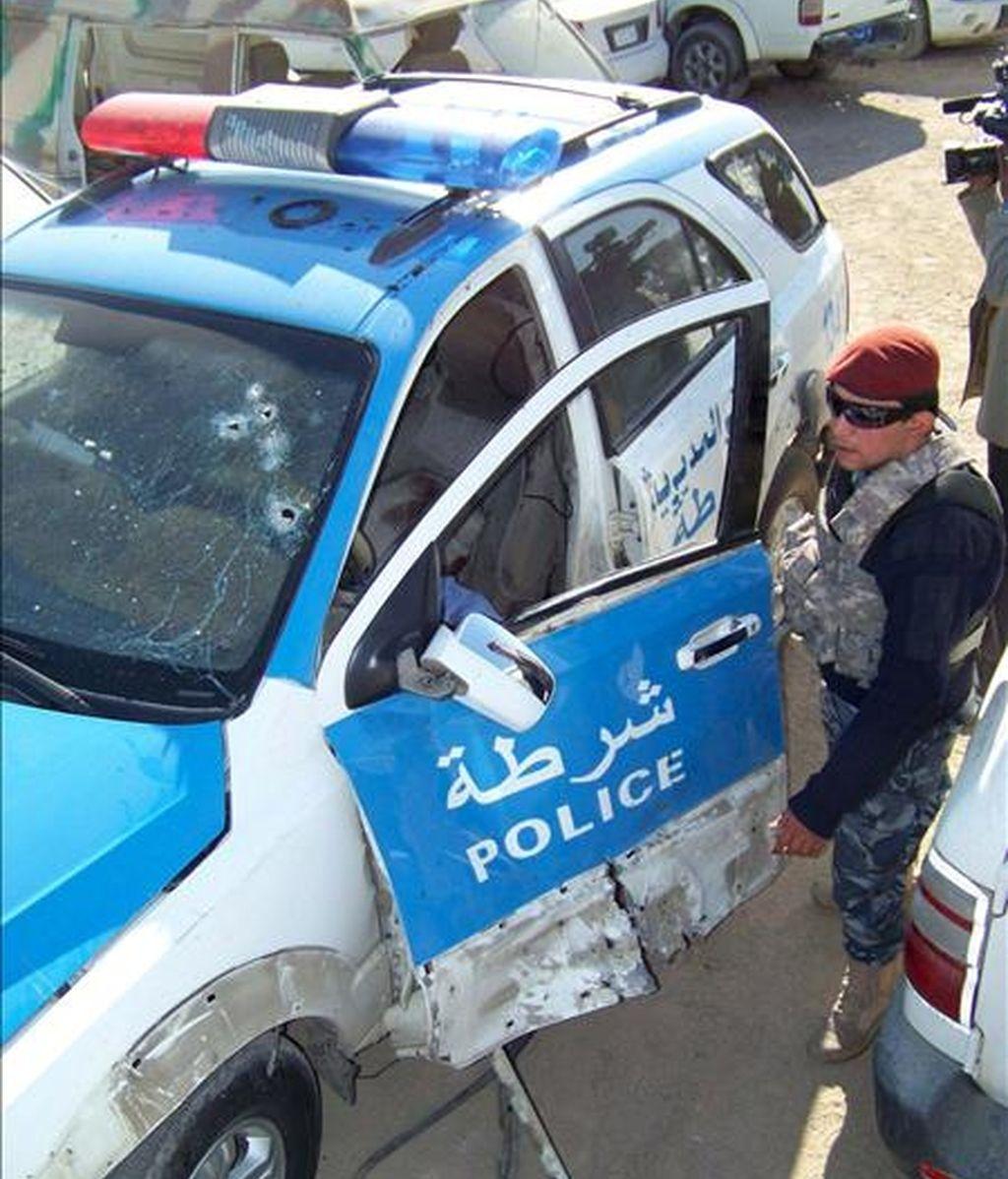 Un policía iraquí inspecciona los daños registrados en un vehículo policial tras la explosión de una bomba en el centro de Basora, al sur de Irak, el pasado 29 de diciembre. EFE/Archivo