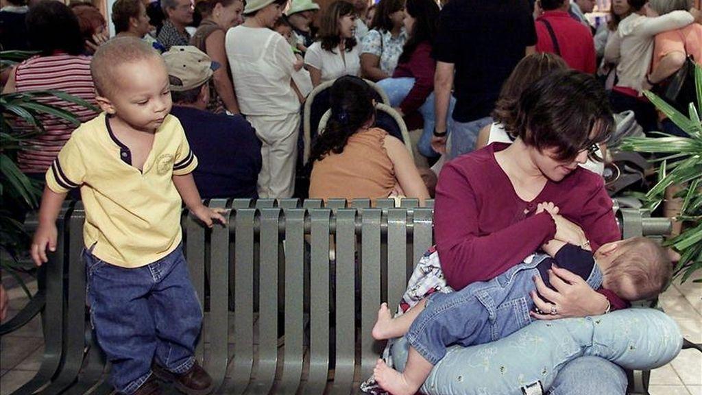 Un niño mira a una madre mientras da de mamar a su bebé. EFE/Archivo
