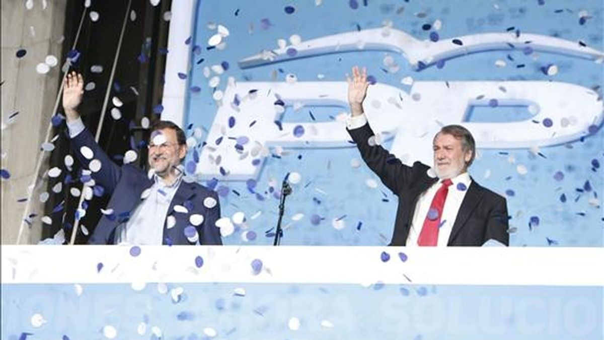 El candidato del Partido Popular, Jaime Mayor Oreja (d), y el presidente del partido, Mariano Rajoy, saludan a los simpatizantes, anoche, desde la sede de los populares en Madrid antes de comentar los resultados de las elecciones al parlamento europeo. EFE