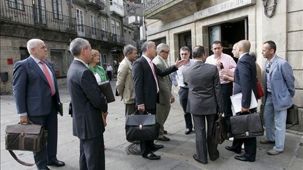 Directivos de Caixa Galicia y Caixanova y los representantes de los sindicatos conversan antes de mantener una reunión para abordar la reorganización laboral de ambas entidades tras la fusión. EFE