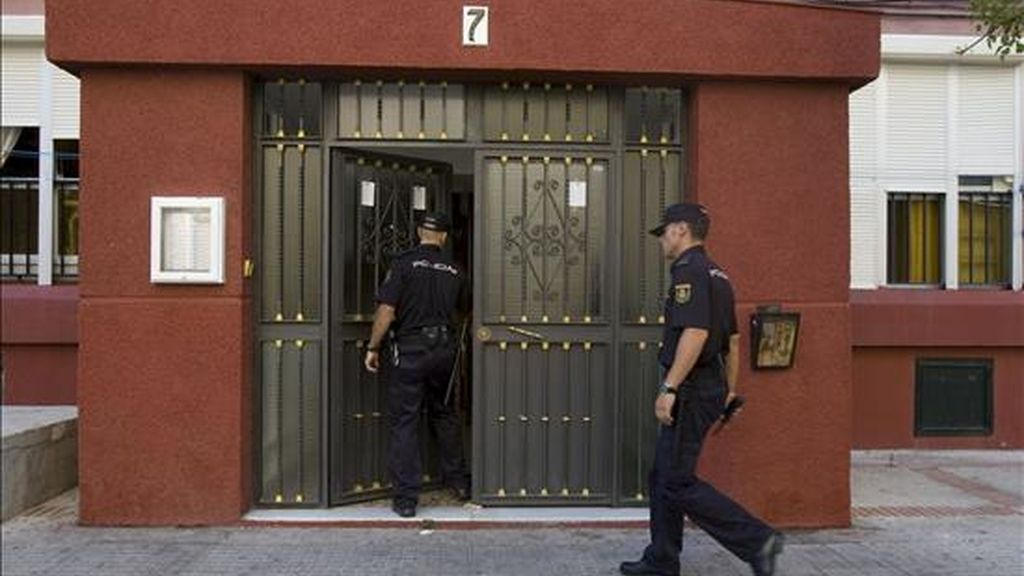 Agentes de la Policía en el bloque de Cádiz donde hoy ha sido hallado el cadáver de una mujer de 55 años con más de 30 puñaladas. EFE