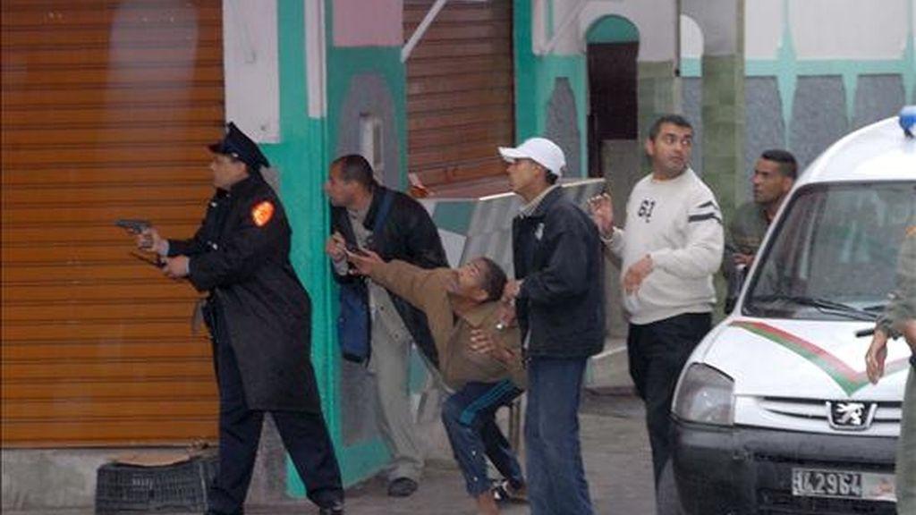 En la imagen, un policia marroquí empuña una pistola frente a la casa donde un hombre fue detenido tras amenazar con hacer estallar un artefacto en el barrio Al Farah de Casablanca, Marruecos. EFE/Archivo