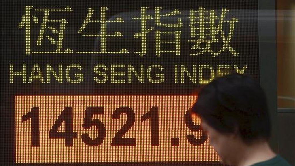 Una mujer camina cerca de un panel electrónico de un banco que muestra el índice de la bolsa de Hang Seng en la ciudad de Hong Kong. EFE/Archivo