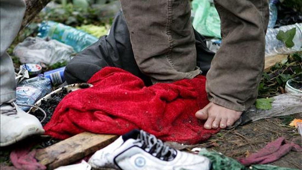 """Un inmigrante ilegal descalzo en su campamento """"La Selva"""" a las afueras de Calais (Francia). Cientos de ilegales, principalmente provenientes de Afganistán e Irak, pasan el tiempo en esta ciudad esperando poder viajar al Reino Unido. La policía ha detenido en las últimas horas a 150 personas que viven en Calais. EFE/Archivo"""