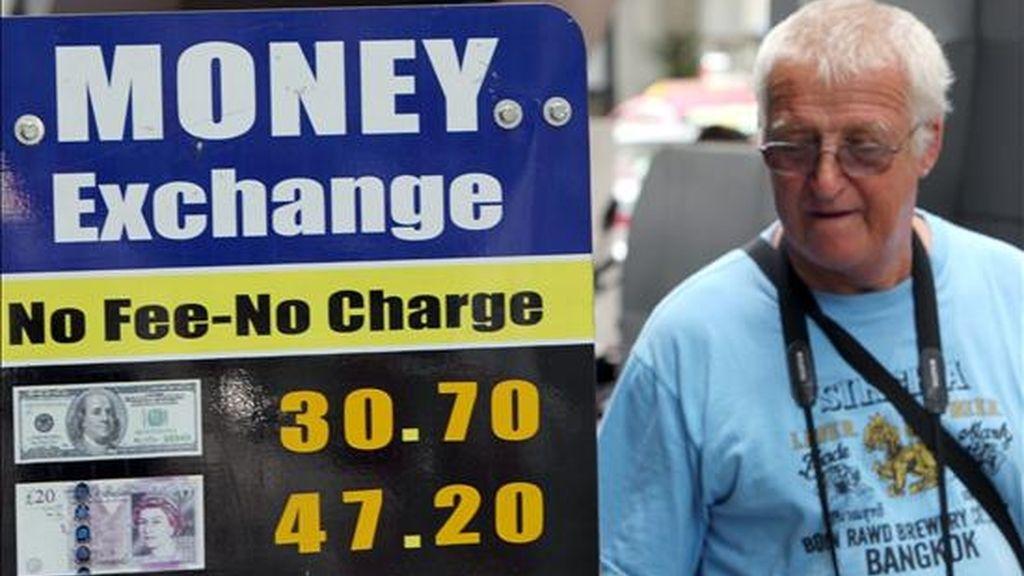 Un turista observa los valores de distintas divisas en el distrito financiero de Bangkok. EFE/Archivo
