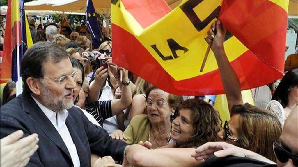 El presidente del PP, Mariano Rajoy (i), saluda a los simpatizantes, durante el encuentro que ha mantenido, hoy en la plaza del Altozano de Albacete, con motivo de los comicios europeos del próximo domingo. EFE