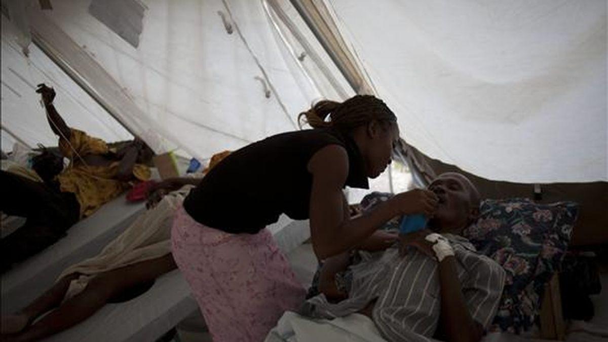 Una mujer da de beber a un paciente de cólera el 22 de noviembre de 2010, en el hospital Bicentenaire, en el Bulevar La Saline, en Puerto Príncipe (Haití). EFE