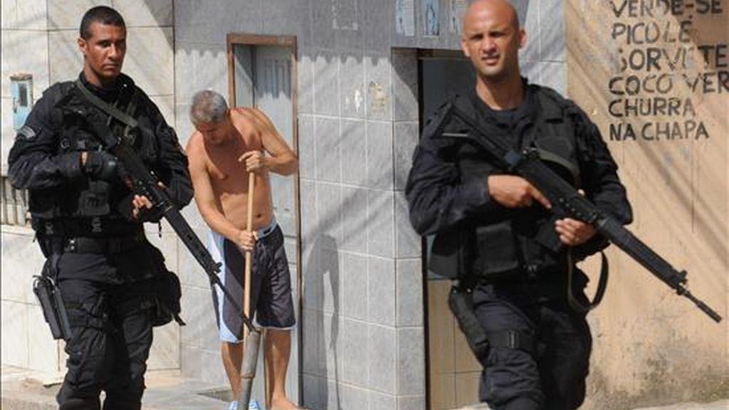 Dos policías patrullan una calle de la favela Grota mientras un hombre asea el frente de una casa este 29 de noviembre un día después de que las fuerzas de seguridad tomaran varias barriadas en Río de Janeiro (Brasil). EFE