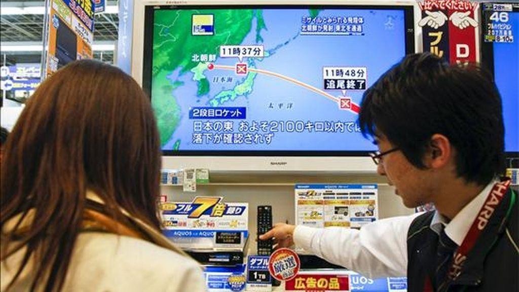 Clientes observan una pantalla de televisión que muestra un mapa con la trayectoria del satélite de comunicaciones norcoreano lanzado, en una tienda de electrónica en Seúl. EFE/Archivo