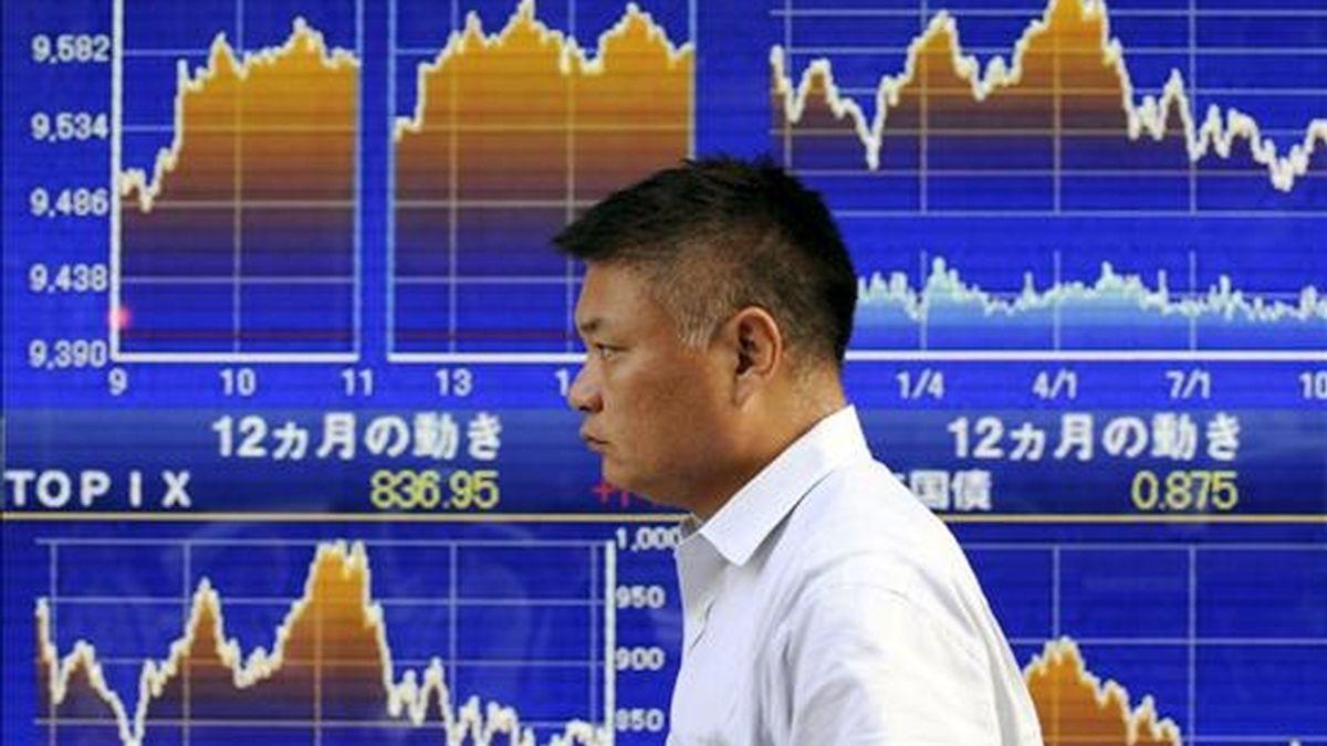 Un hombre pasa por delante de una pantalla electrónica con los resultados bursátiles, en Tokio. EFE/Archivo