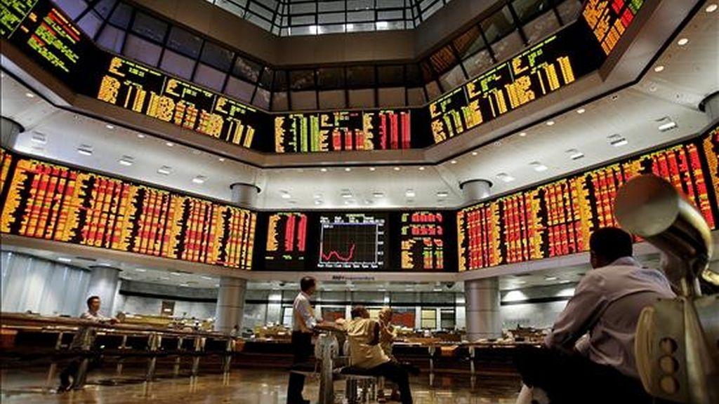 Inversores malayos observan los paneles electrónicos de una oficina de operaciones bursátiles en Kuala Lumpur (Malasia). Los parqués del Sudesete Asiátiaco iniciaron hoy la jornada bursátil en positivo, salvo la bolsa de Ho Chi Minh que empezó con pérdidas. EFE/Archivo
