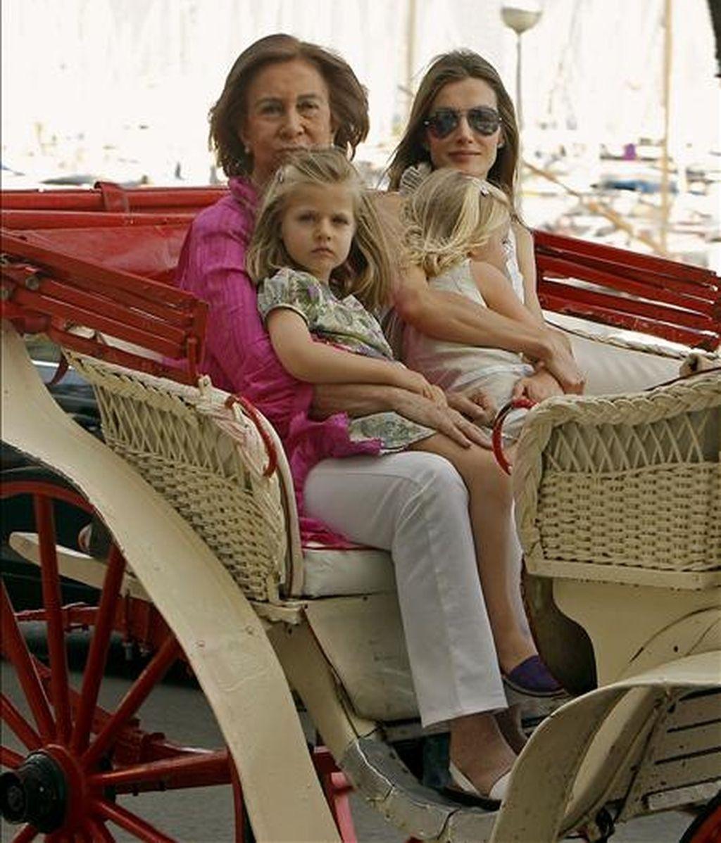 La Reina Sofía, acompañada por la princesa Letizia y las infantas Leonor y Sofía, durante el paseo en calesa que han realizado esta tarde por las calles de Palma de Mallorca. EFE