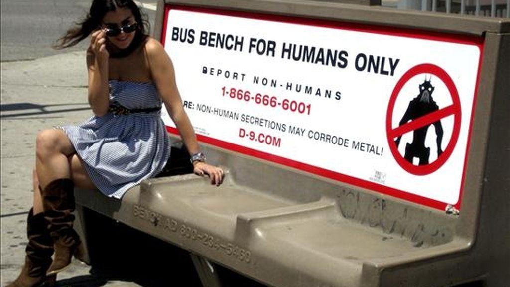 """Una mujer permanece sentada junto a un letrero promocional de la película """"District 9"""" que dice """"Banca de bus sólo para humanos"""", en Los Ángeles. El anuncio hace parte de una campaña publicitaria para el filme. EFE"""