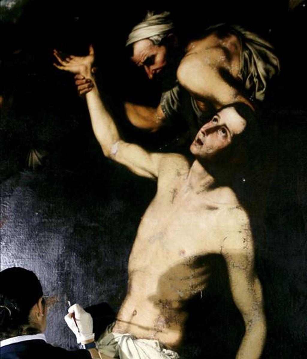"""Los restauradores de los retablos del Nazareno y de la Santisima Trinidad de la catedral de Granada han descubierto tres cuadros excepcionales del pintor valenciano José de Ribera , """"el Españoleto"""", uno de los máximos exponentes de la pintura española. En la imagen, una restauradora trabaja en el cuadro de San Lorenzo. EFE"""