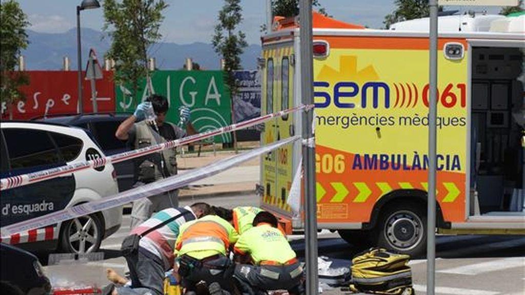 Miembros de los equipos de emergencia tratan de reanimar al conductor muerto por otro conductor este mediodía a la entrada de Figueres golpeándole con un gato de coche cuando discutían después de chocar los vehículos que conducían. EFE