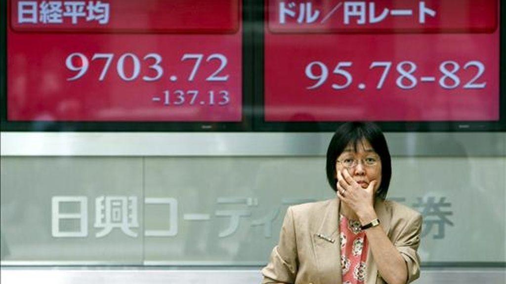 Una mujer japonesa delante de una pantalla de información bursátil en Tokio. EFE/Archivo