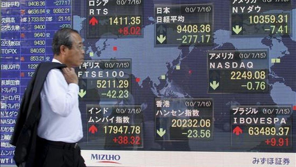 Un empresario pasa junto a una pantalla con los resultados de la Bolsa de Tokio (Japón). EFE (Archivo)