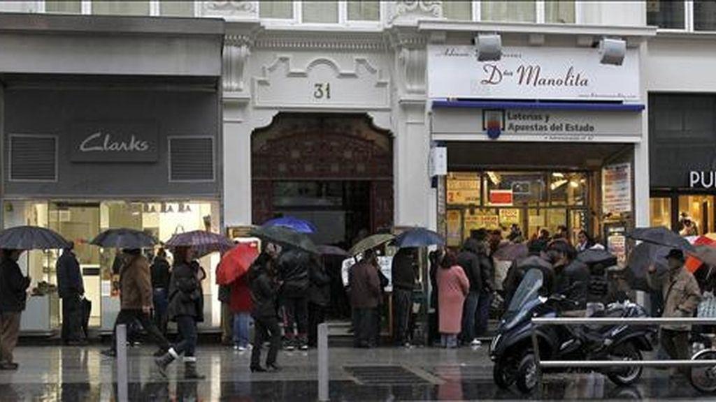 """Decenas de personas que esperan su turno para comprar lotería en una administración en la Gran Vía de Madrid se cubren de la lluvia con un paraguas por el temporal atlántico que afecta a la Península Ibérica, caracterizado por una masa de aire """"húmeda y cálida"""", que comenzará a remitir a partir de mañana. EFE"""