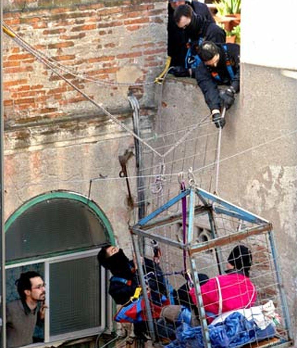 Varios mossos d'esquadra tratan de soltar a un joven que se ha encerrado en un jaula colgada en el patio interior. Foto: EFE.