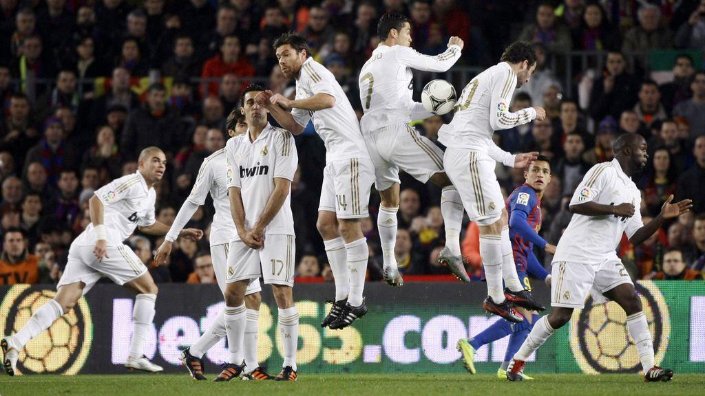 Los jugadores del Real Madrid salta para detener un tiro libre de Alves