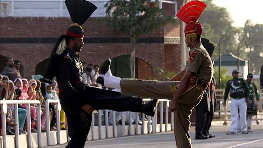 """Un soldado indio de la Fuerza de Seguridad de la Frontera y otro de las fuerzas paquistaníes durante la ceremonia militar """"Beating the Retreat"""", de origen británico, en el puesto fronterizo de Attari. EFE/Archivo"""