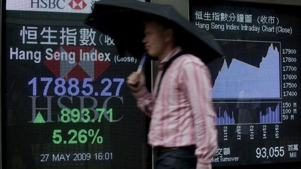 Un hombre pasa por delante de una pantalla en la que se reflejan los valores de la Bolsa, en Hong Kong. EFE/Archivo