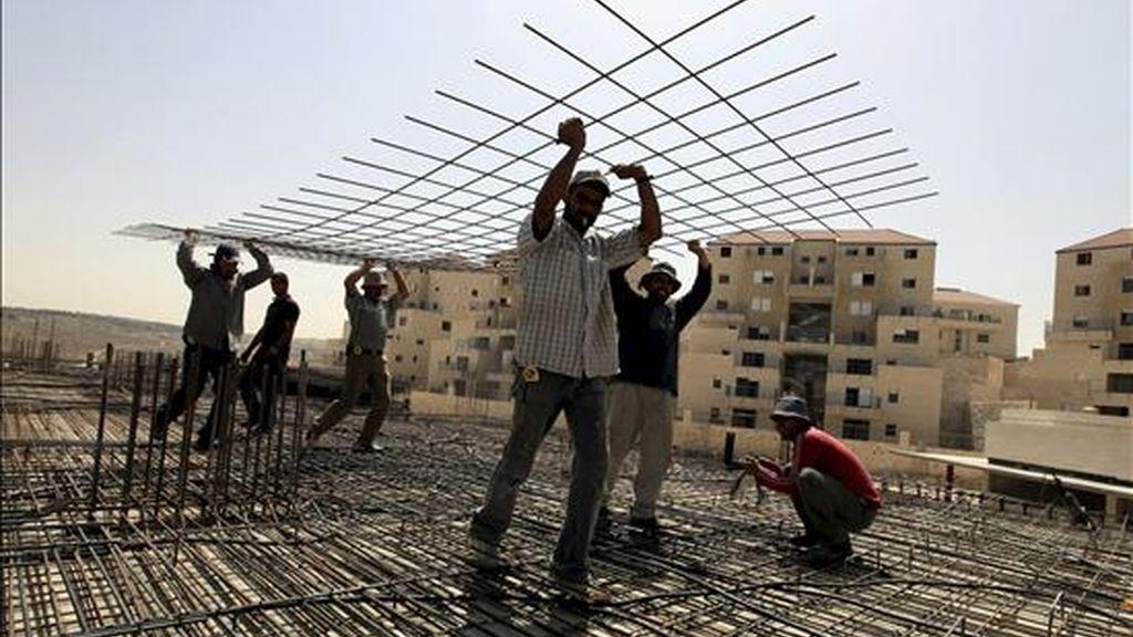 Obreros palestinos construyen el tejado de un edificio de viviendas en el asentamiento judio de Beitar Illit, Cisjordania, el pasado 10 de junio. EFE/Archivo