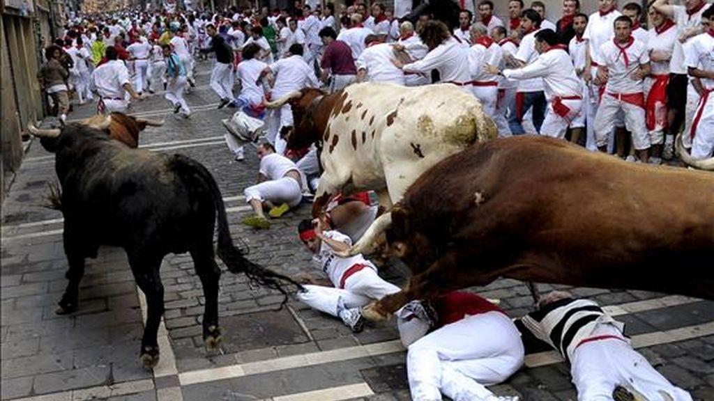 Varios mozos caen ante los toros de la ganadería salmantina de El Pilar en la curva de Mercaderes durante el séptimo encierro de los Sanfermines 2010. EFE