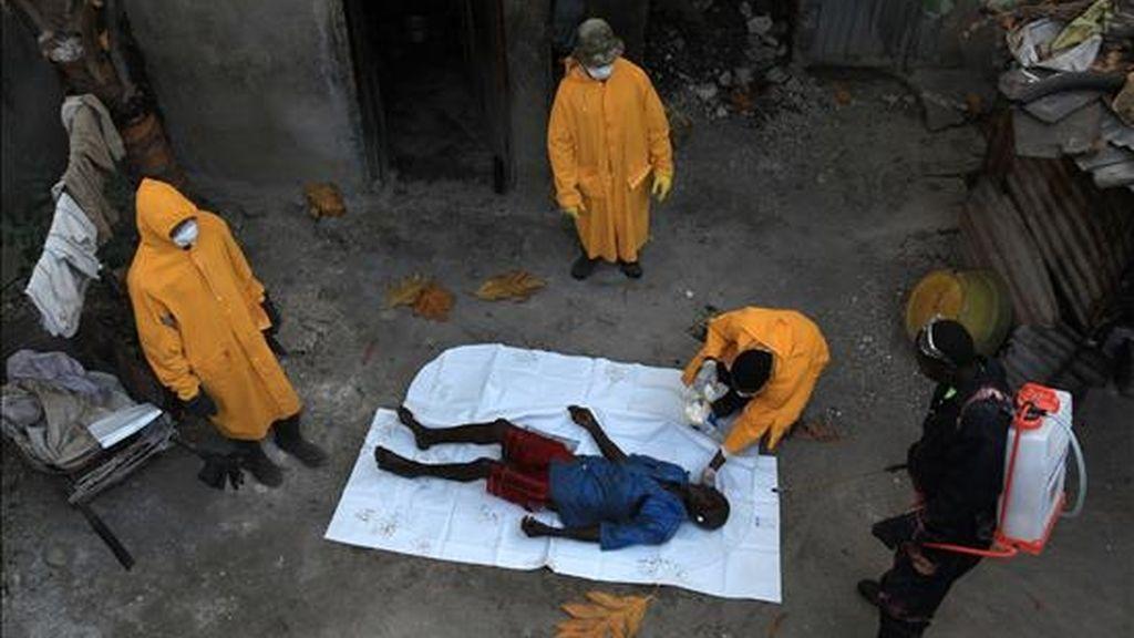 Miembro del personal de salud pública de Haití se preparan para trasladar el cadavér de una víctima de cólera el 27 de noviembre de 2010, en Puerto Príncipe (Haití). La ONU ha pedido 7.400 millones de dólares para asistir a 50 millones de personas. EFE/Archivo
