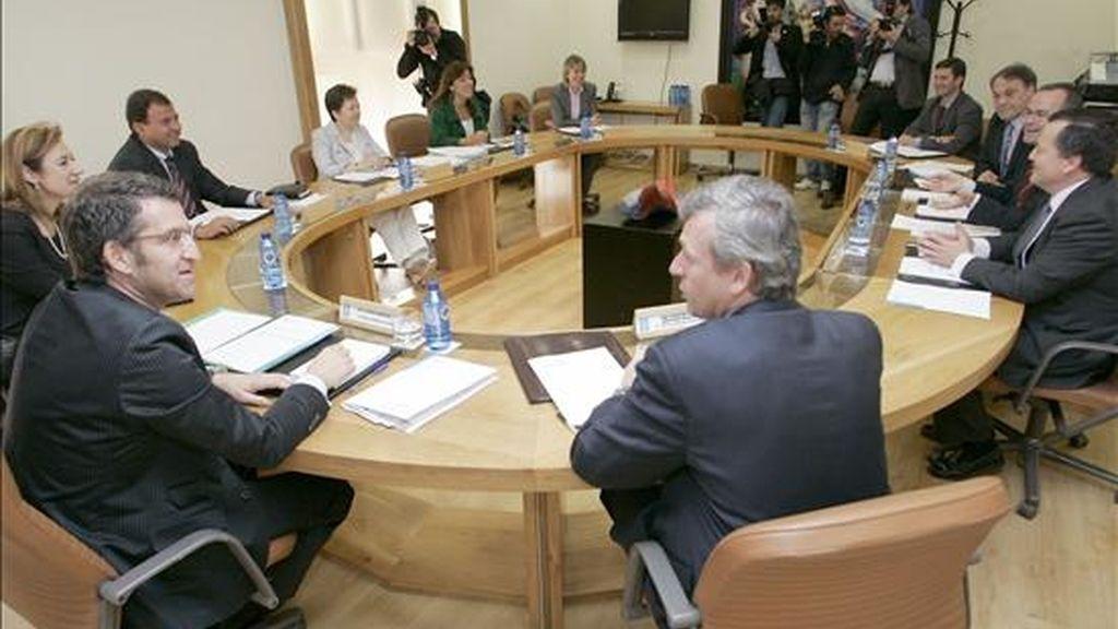 El presidente de la Xunta de Galicia, Alberto Núñez Feijoo, conversa al inicio de la reunión del Ejecutivo gallego, en la que se aprobó el Decreto que reduce en un 47 por ciento el número de altos cargos en la Administración, hoy en el Parlamento regional. EFE