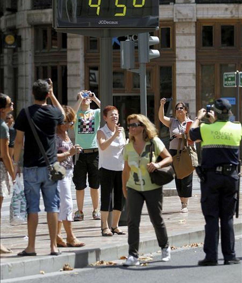 Un grupo de turistas y un policía local hacen fotos de un termómetro situado en el centro de la capital, que marca 45 grados. EFE/Archivo