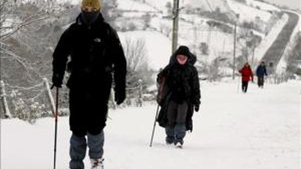 Un grupo de peregrinos camina esta mañana hacia Santiago de Compostela, junto a la carretera LU-633, en Pedrafita do Cebreiro, tras la intensa nevada de la pasada noche. EFE
